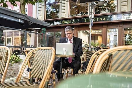 Der Investment-Banker Thorsten Müller bereitet sich in einem Cafe in der Bankenmetropole Frankfurt am Main auf eine Video-Konferenz vor. Foto: Frank Rumpenhorst/dpa-tmn