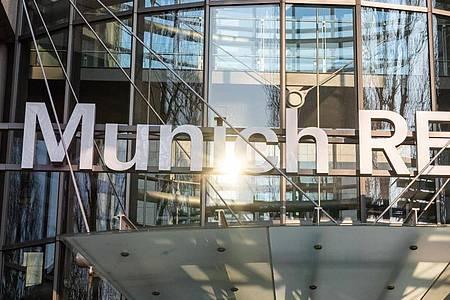 Das Logo der Munich RE am Haupteingang des Verwaltungsgebäudes der Münchener Rückversicherungs-Gesellschaft AG. Foto: Peter Kneffel/dpa