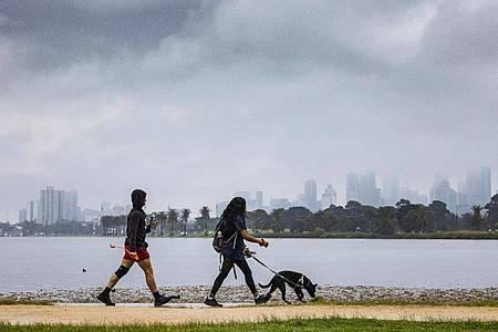 Menschen gehen mit einem Hund am Albert Park Lake in Melbourne spazieren. (Archivbild). Foto: Daniel Pockett/AAP/dpa