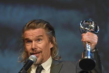 Ethan Hawke mit seiner Auszeichnung beim Internationalen Karlsbader Filmfestival. Foto: Kubeš Slavomír/CTK/dpa