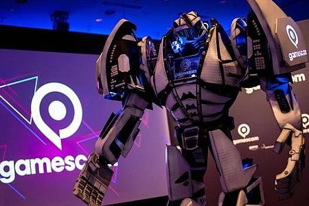 Gamesbot, das Maskottchen der Gamescom, steht während einer Pressekonferenz vor der Bühne. Foto: Marius Becker/dpa