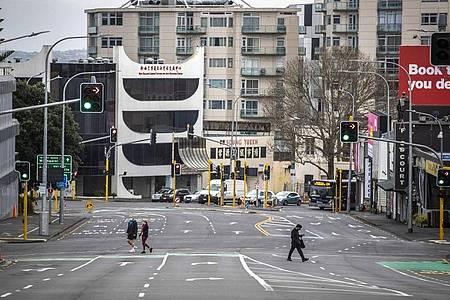 Menschen überqueren im zentralen Geschäftsviertel in Auckland fast leere Straßen. Foto: Michael Craig/New Zealand Herald/dpa