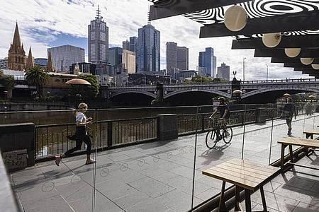 Menschen joggen entlang der Southgate in Melbourne. Gut eineinhalb Jahre nach Beginn der Corona-Pandemie hat die australische Millionenmetropole einen unrühmlichen Rekord aufgestellt: 246 Tage im Lockdown-Modus. Foto: Daniel Pockett/AAP/dpa