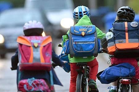 Kinder sind auf einer Straße mit dem Fahrrad unterwegs zur Schule. Symbolbild. Foto: Ralf Hirschberger/dpa-Zentralbild/dpa