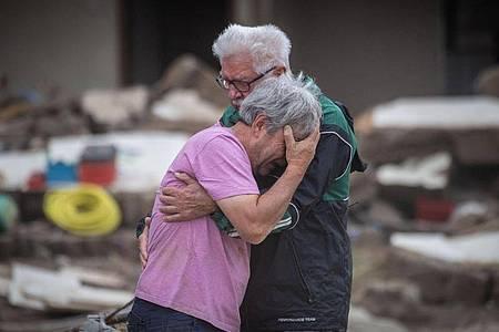 Weinend liegen sich die Brüder Bernd (l) und Gerd Gasper vor ihrem von der Flut zerstörten Elternhaus in Altenahr in den Armen. Foto: Boris Roessler/dpa