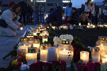 Personen zünden Kerzen an in Gedenken an die Opfer. Nach der Gewalttat mit fünf Toten im norwegischen Kongsberg soll der Tatverdächtige am Freitag einem Haftrichter vorgeführt werden. Foto: Terje Bendiksby/NTB/dpa