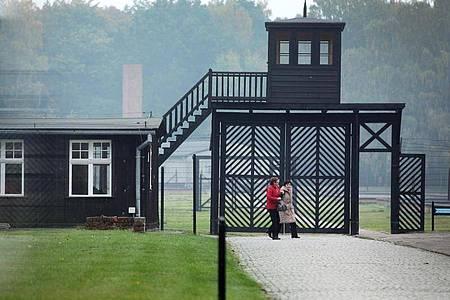 Besucher gehen am Eingang des Stutthof Museums in Sztutowo (Polen) vorbei, in dem an die Verbrechen im ehemaligen deutschen Konzentrationslager Stutthof erinnert wird. Foto: Piotr Wittman/PAP/dpa