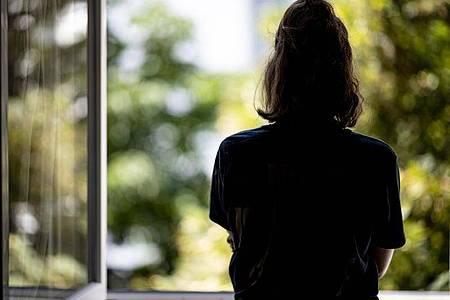 Eine Frau steht in ihrer Wohnung an einem Fenster. (Archivbild). Foto: Fabian Sommer/dpa