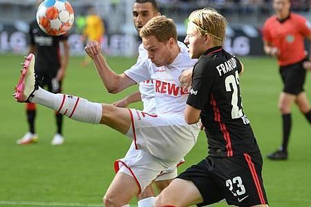 Kölns Benno Schmitz (l) kommt vor Frankfurts Jens Petter Hauge an den Ball. Foto: Arne Dedert/dpa