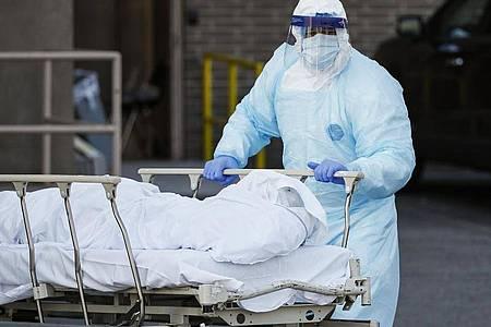 Ein Mitarbeiter in Schutzkleidung bringt eine Leiche zu einem Kühlanhänger, der als behelfsmäßige Leichenhalle im Wyckoff Heights Medical Center in New York dient. Foto: John Minchillo/AP/dpa