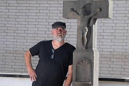 Wolfgang Ewerts neben dem mittlerweile wieder aufgestellten Opferstock vor seinem Hotel in Insul. Foto: Boris Roessler/dpa