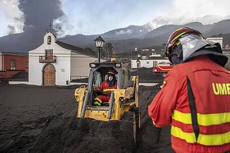 Einsatzkräfte des Militärs entfernen schwarze Asche vom Vulkan, der hinter der kleinen Kirche auf der Kanareninsel La Palma weiter Lava ausstößt. Foto: Saul Santos/AP/dpa