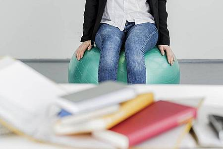 Ein Gymnastikball hat gegenüber einem verstellbaren Bürostuhl mehr Nachteile als Vorteile, kann aber für kurze Zeit hilfreich sein. Foto: Monique Wüstenhagen/dpa-tmn