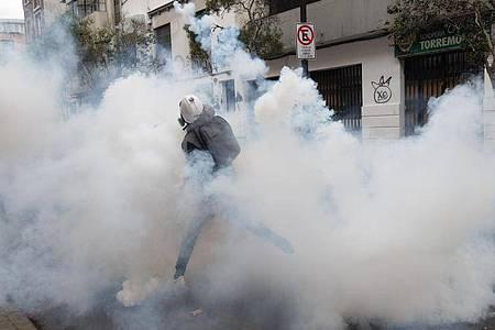 Ein Demonstrant wirft einen Tränengaskanister zurück, der von der Polizei abgefeuert wurde, um einen Protest in Santiago aufzulösen. Foto: Matias Basualdo/ZUMA Press Wire/dpa