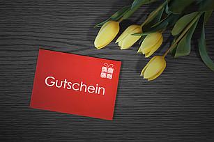 Gutschein und Tulpen auf einem Tisch