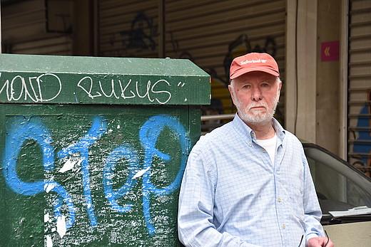 Mann steht vor einem Müllkontainer.
