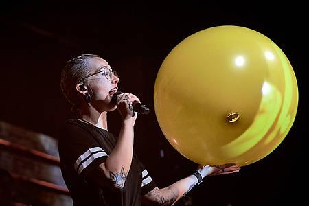 Frau häkt großen gelben Luftballon in die Kamera