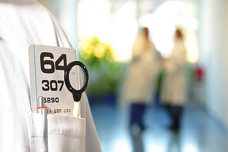 Nahaufnahme eines Arztkittels mit Brusttasche, die eine Lupe enthält