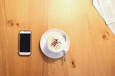 Tasse Kaffee und Handy liegen auf dem Tisch