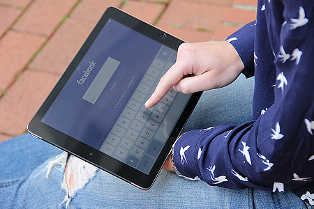 Hand die auf Tablet in der Facebook App tippt