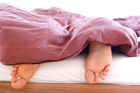 Füße die unter einer Bettdecke hervorgucken